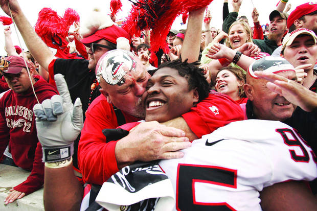 Georgia fan Mike Woods, left, kisses Georgia player Jeff Owens after the Bulldogs defeated No. 5 Auburn 37-15 in a college football game in Auburn, Ala., in 2006. AP Archive Photo