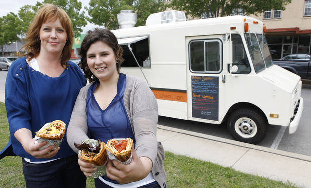 Tara Taylor and Rachel Smith show off their waffle prowess in front of the truck where they make the specialties. <strong>David McDaniel - The Oklahoman</strong>