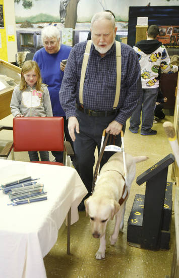 Ralph Haney, president of the Oklahoma Guide Dogs Alumni Association, demonstrates the abilities of his guide dog Tallis to Dacia Sims, 9, at Martin Park Nature Center in Oklahoma City <strong>PAUL HELLSTERN - Oklahoman</strong>
