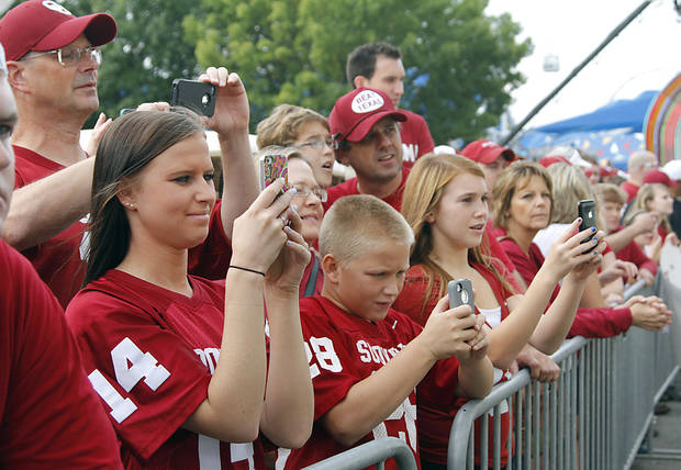 Sooner fans use their cell phones to try and get a photo of their favorite players that arrive during the Red River Rivalry college football game between the University of Oklahoma (OU) and the University of Texas (UT) at the Cotton Bowl in Dallas, Saturday, Oct. 13, 2012. Photo by Chris Landsberger, The Oklahoman