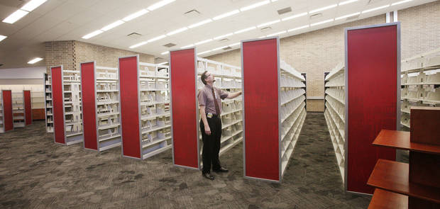 Randy Wayland, branch manager, looks at new book shelves Wednesday inside the remodeled Southern Oaks Library in south Oklahoma City.  Photo by Paul B. Southerland, The Oklahoman