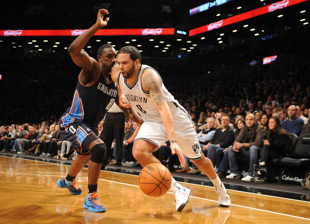Brooklyn Nets point guard Deron Williams (8) drives the ball around Charlotte Bobcats'  Ben Gordon (8) in the first half of an NBA basketball game on Friday, Dec., 28, 2012 at Barclays Center in New York. (AP Photo/Kathy Kmonicek)