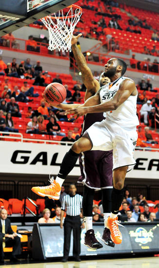 Oklahoma State guard Brian Williams adjusts mid-air to avoid a defender during Oklahoma State's exhibition game versus Campbellsville on Oct. 27, 2013 at Gallagher Iba Arena in Stillwater, Okla. The Cowboys won 80-70, lead by Markel Brown's 13 points. Photo by KT King/For the Oklahoman
