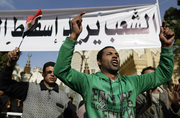Egyptian protesters chant anti-Muslim Brotherhood and Egyptian President Mohammed Mosri slogans outside the presidential palace under a banner with a defaced picture of President Mohammed Morsi and Arabic that reads &quot;the people want to bring down the regime,&quot; at the protests site, in Cairo, Egypt, Saturday, Dec. 8, 2012. Egypt&#039;s military has warned of &#039;disastrous consequences&#039; if the political crisis gripping the country is not resolved through dialogue. (AP Photo/Hassan Ammar)