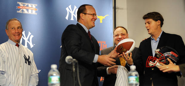 New York Yankees' managing general partner Hal Steinbrenner, right, receives a football and helmet from Big 12 commissioner Dan Beebe, second from left, as Big East commissioner John Marinatto, second from right, and New York City Mayor Michael Bloomberg, left, look on, during a news conference, Wednesday, Sept. 30, 2009 at Yankee Stadium in the Bronx borough of New York.  The NCAA college football conferences and the New York Yankees announced on Wednesday that they have agreed to a four-year deal to play the first bowl in the Bronx since 1962. (AP Photo/Stephen Chernin) ORG XMIT: NYSC104