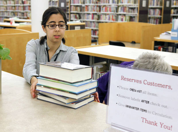 Library Aide Juliet Alavicheh shelves reserved books Friday as a part of the new self-serve reserve system at the Edmond branch of the Metropolitan Library System. Photos By Paul Hellstern, The Oklahoman