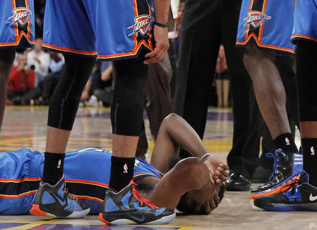 Oklahoma City Thunder players stand over teammate James Harden, lower left, after receiving a flagrant double foul from Los Angeles Lakers' Metta World Peace, who was then ejected, in the first half of an NBA basketball game, Sunday, April 22, 2012, in Los Angeles. (AP Photo/Reed Saxon)