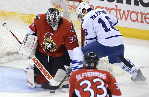 Ottawa Senators goalie Ben Bishop, left, stops a shot from Toronto Maple Leafs' Clarke MacArthur during the first period of an NHL hockey game in Ottawa, Ontario, on Saturday, Feb. 23, 2013. (AP Photo/The Canadian Press, Sean Kilpatrick)