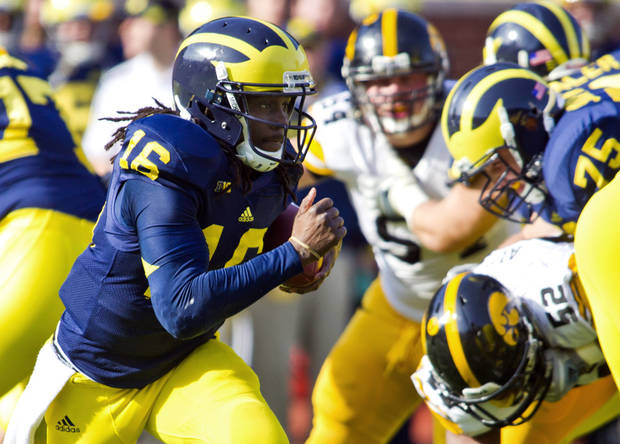 Michigan quarterback Denard Robinson (16) rushes in the first quarter of an NCAA college football game against Iowa, Saturday, Nov. 17, 2012, in Ann Arbor, Mich. (AP Photo/Tony Ding)