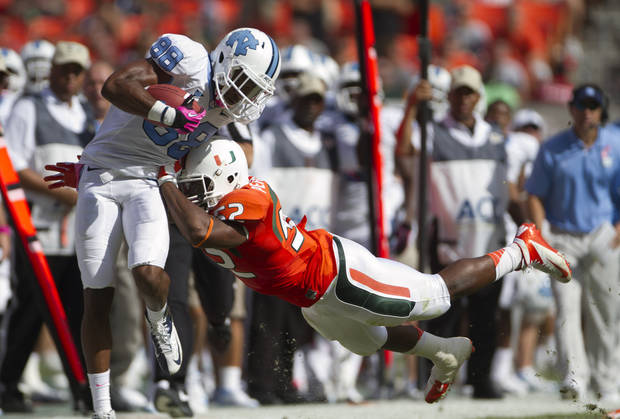 Miami's Denzel Perryman (52) tries to knock North Carolina's Erik Highsmith (88) out of bounds during the first half of a NCAA college football game in Miami, Saturday, Oct. 13, 2012. (AP Photo/J Pat Carter)