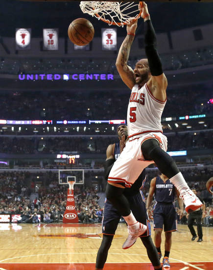 Chicago Bulls forward Carlos Boozer (5) dunks in front of Charlotte Bobcats forward Hakim Warrick during the first half of an NBA basketball game Monday, Dec. 31, 2012, in Chicago. (AP Photo/Charles Rex Arbogast)