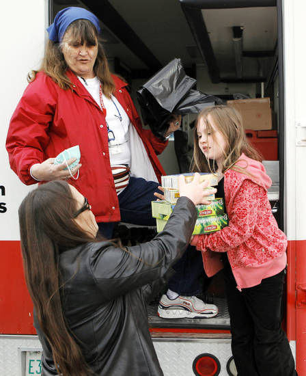 Red Cross volunteer Liz McKeel, upper left, gives relief items to Christina Myers, bottom left, and her daughter, Braylin Stilwell-Love, 8, Monday at a Red Cross field office in Midwest City. Photo by Nate Billings, The Oklahoman