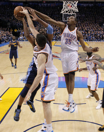 Oklahoma City's Kevin Durant (35) and Nick Collison (4) defend Denver's Nene (31) during the NBA basketball game between the Denver Nuggets and the Oklahoma City Thunder in the first round of the NBA playoffs at the Oklahoma City Arena, Wednesday, April 27, 2011. Photo by Bryan Terry, The Oklahoman