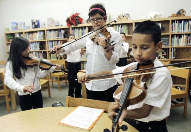 From left, Amy Barron, Hannah Geeslin and Saul Ortiz play violins during a mariachi class Tuesday at Fillmore Elementary School in Oklahoma City. Photos by Paul Hellstern, The Oklahoman