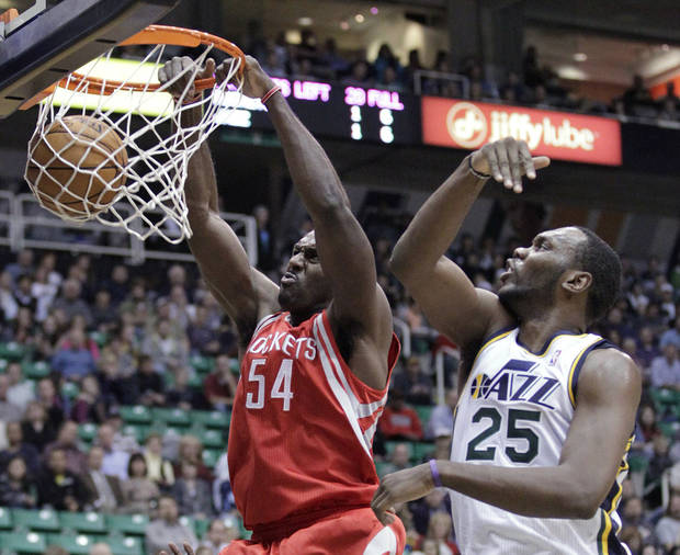 Houston Rockets forward Patrick Patterson (54) dunks as Utah Jazz center Al Jefferson (25) defends in the first quarter during an NBA basketball game Monday. Nov. 19, 2012, in Salt Lake City. (AP Photo/Rick Bowmer)