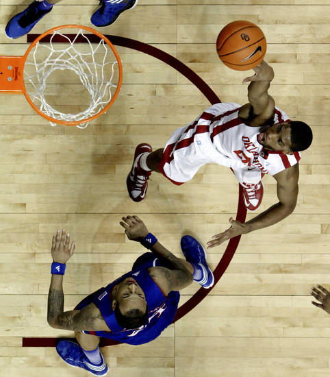Oklahoma's Cameron Clark (21) shoots guarded by Kansas' Travis Releford (24) during the second half as the University of Oklahoma Sooners (OU) defeat the Kansas Jayhawks (KU) 72-66 in NCAA, men's college basketball at The Lloyd Noble Center on Saturday, Feb. 9, 2013 in Norman, Okla. Photo by Steve Sisney, The Oklahoman