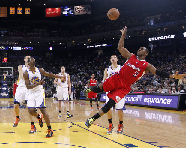 Los Angeles Clippers' Chris Paul (3) scores on an off-balance shot past Golden State Warriors' Harrison Barnes (40) and Klay Thompson, behind Paul, during the first half of an NBA basketball game in Oakland, Calif., Monday, Jan. 21, 2013. (AP Photo/Marcio Jose Sanchez)