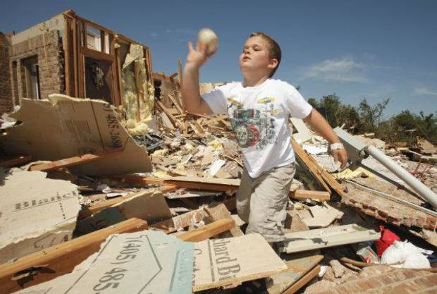 Briggs Bewley, 6, throws a baseball he found in the rubble of his home in Blanchard. PHOTO BY STEVE SISNEY, THE OKLAHOMAN <strong>STEVE SISNEY</strong>