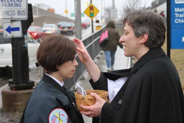 The Rev. Kara Wagner Sherer, of St. John�s Episcopal Church in Chicago, places ashes on a passer-by in 2011 as part of a growing �Ashes to Go� program in the Episcopal Church. Numerous Episcopal churches across the country participated in the program this year. RNS Photo