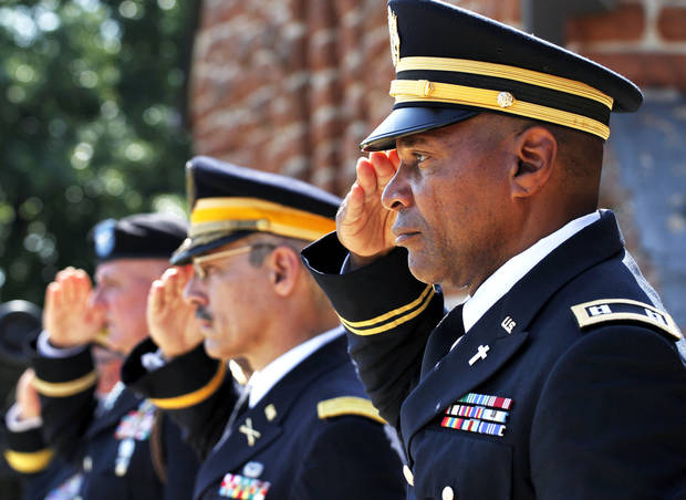 Platform dignitaries, including Chaplain (Capt.) James Smith, foreground, salute while standing at attention during the wreath laying  at the Memorial Day Ceremony on the grounds of the 45th Infantry Division Museum  on Monday,  May 28,  2012,  Photo by Jim Beckel, The Oklahoman