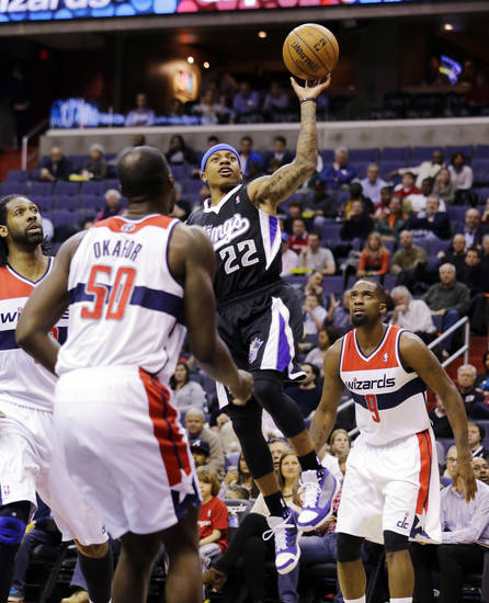 Sacramento Kings guard Isaiah Thomas (22) shoots between Washington Wizards center Nene, left, of Brazil, center Emeka Okafor (50)  and forward Martell Webster (9) in the first half of an NBA basketball game, Monday, Jan. 28, 2013, in Washington. (AP Photo/Alex Brandon)