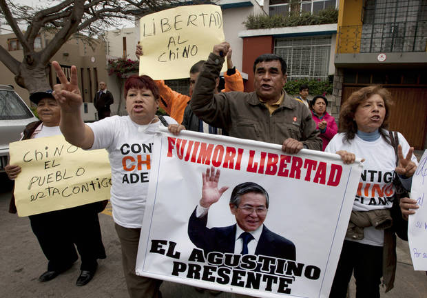 "Supporters of Peru's former and jailed President Alberto Fujimori shout slogans outside the Justice Ministry building with signs that read in Spanish ""Free Fujimori"" in Lima, Peru, Wednesday, Oct. 10, 2012. Fujimori's children delivered a document to the justice ministry seeking their father's pardon for humanitarian reasons, citing his health. The 74-year-old Fujimori is serving a 25-year sentence for crimes against humanity related to death-squad killings during his rule in the 1990s. (AP Photo/Martin Mejia)"