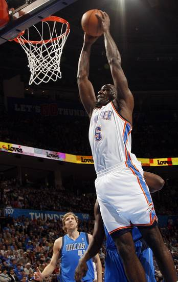 Oklahoma City's Kendrick Perkins (5) dunks the ball in front of Dallas' Dirk Nowitzki (41) during the NBA basketball game between the Oklahoma City Thunder and the Dallas Mavericks at Chesapeake Energy Arena in Oklahoma City, Monday, March 5, 2012. Photo by Nate Billings, The Oklahoman