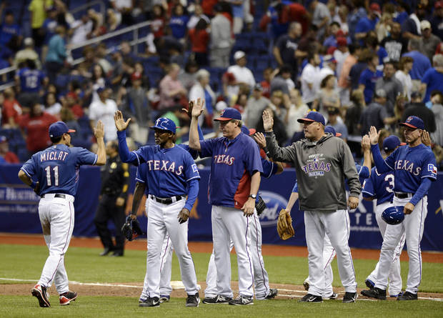 Texas Rangers coaches congratulate players on their 5-2 win over the San Diego Padres after an exhibition baseball game,, Saturday, March 30, 2013, at the Alamodome in San Antonio. (AP Photo/Darren Abate)
