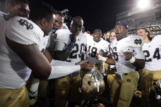 Notre Dame players, including Kendall Moore, left, Cierre Wood (20), Davonte' Neal (19), Theo Riddick and Chris Salvi (24) celebrate following a 20-3 win over Michigan State in an NCAA college football game, Saturday, Sept. 15, 2012, in East Lansing, Mich. (AP Photo/Al Goldis) ORG XMIT: ELJ112