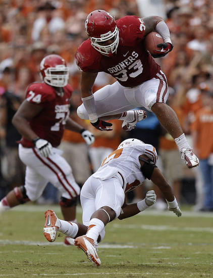 OU&#039;s Trey Millard (33) leaps over UT&#039;s Adrian Phillips (17) during the Red River Rivalry college football game between the University of Oklahoma (OU) and the University of Texas (UT) at the Cotton Bowl in Dallas, Saturday, Oct. 13, 2012. Photo by Bryan Terry, The Oklahoman