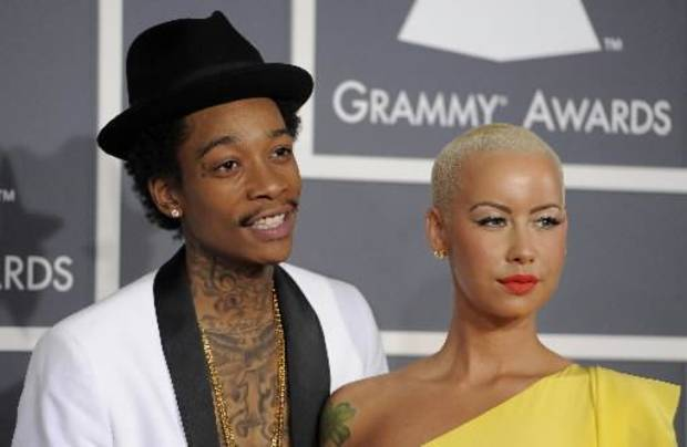 "This Feb. 12, 2012 file photo shows Wiz Khalifa, left, and Amber Rose at the 54th annual Grammy Awards in Los Angeles. Khalifa says the preparation of becoming a first-time father and husband has helped put him in a more mature musical state of mind. ""I'm at a different point of my life,"" said Khalifa, whose sophomore album, ""O.N.I.F.C.,"" debuted at No. 2 on Billboard's 200 albums chart Wednesday with more than 141,000 copies sold, according to Nielsen Scan. (AP Photo/Chris Pizzello, file)"
