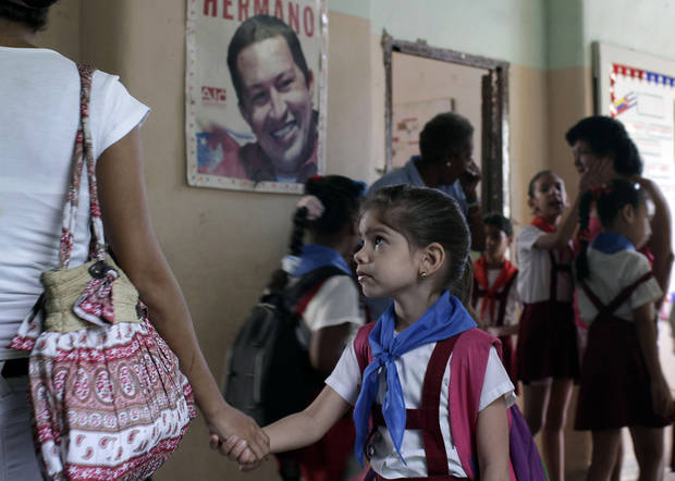 A student holds her teacher's hand at the start of the school day at the Bolivarian Republic of Venezuela school where a poster of Venezuela's President Hugo Chavez hangs on the wall in Havana, Cuba, Wednesday, Dec. 12, 2012. Chavez was recovering in Cuba on Tuesday after an operation targeting an aggressive cancer that has defied multiple treatments and has prompted the socialist leader to name a political successor. (AP Photo/Franklin Reyes)