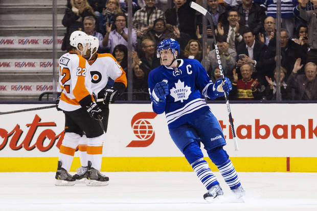 Toronto Maple Leafs' Dion Phaneuf, right, celebrates his goal as Philadelphia Flyers' Luke Schenn (22) and Wayne Simmonds skate by during the first period of their NHL hockey game, Monday, Feb. 11, 2013, in Toronto. (AP Photo/The Canadian Press, Chris Young)