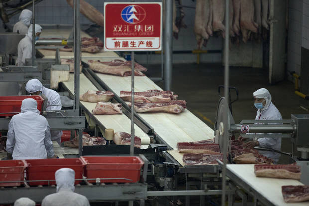 Employees work at a pork processing plant owned by Shuanghui Group Ltd., in Luohe, in central China's Henan province. AP Photo/Alexander F. Yuan <strong>Alexander F. Yuan</strong>