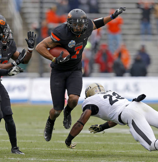 Oklahoma State's Shamiel Gary (7) leaps past Purdue's Ralph Bolden (23) after a interception during the Heart of Dallas Bowl football game between Oklahoma State University and Purdue University at the Cotton Bowl in Dallas, Tuesday, Jan. 1, 2013. Oklahoma State won 58-14. Photo by Bryan Terry, The Oklahoman
