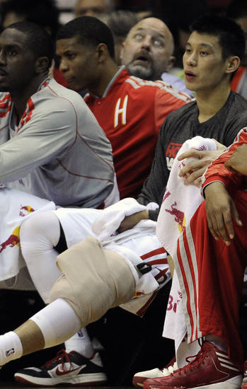 Houston Rockets' Jeremy Lin, right, sits on the bench with ice on his knee in the first quarter of an NBA basketball game against the Portland Trail Blazers, Saturday, Nov. 3, 2012, in Houston. Lin re-entered the game in the second quarter. (AP Photo/Pat Sullivan)