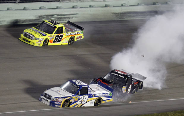 Kyle Larson (4) crashes into Ryan Blaney (29) as Matt Crafton (88) races by during the NASCAR Truck Series auto race at Homestead-Miami Speedway in Homestead, Fla., Friday, Nov. 16, 2012. Cale Gale went on to win the race. (AP Photo/Alan Diaz)