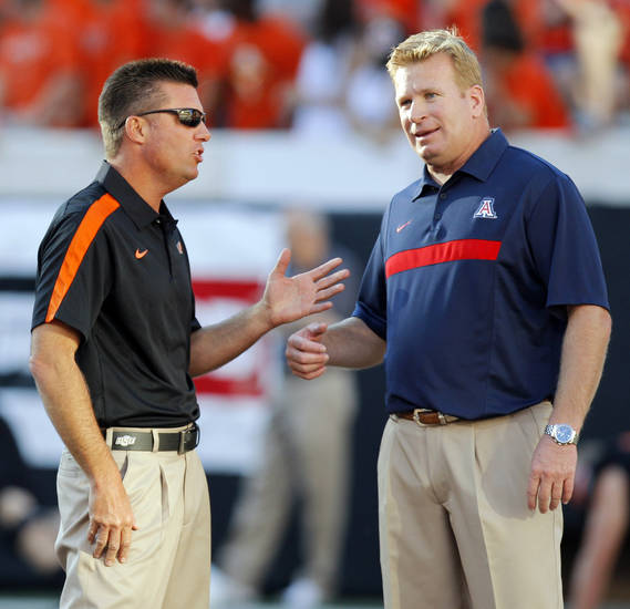 OSU head coach Mike Gundy, left, and Arizona head coach Mike Stoops talk before their game Thursday night in Stillwater. PHOTO BY NATE BILLINGS, The Oklahoman
