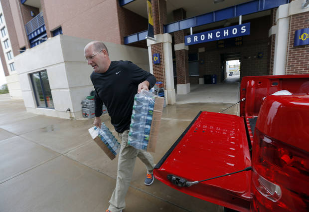 Edmond Public Schools' Athletic Director Mike Nunley carries water up to the press box before a game, Thursday, Sept. 13, 2012. Photo by Sarah Phipps, The Oklahoman