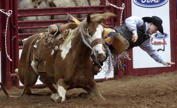 IFR: Jet McCoy of Tupelo Okla., gets thrown from his horse during the Saddle Bronc Riding competition in the International Finals Rodeo at the Ford Center.  Staff photo by Bryan Terry
