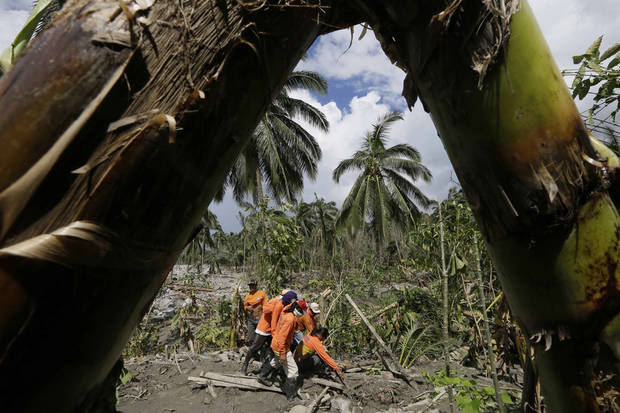 Rescuers prepare to dig up another flash flood victim at the village of Andap, New Bataan township, Compostela Valley in southern Philippines Saturday, Dec. 8, 2012. Search and rescue operations following a typhoon that killed nearly 600 people in the southern Philippines have been hampered in part because many residents of this ravaged farming community are too stunned to assist recovery efforts, an official said Saturday.  (AP Photo/Bullit Marquez)