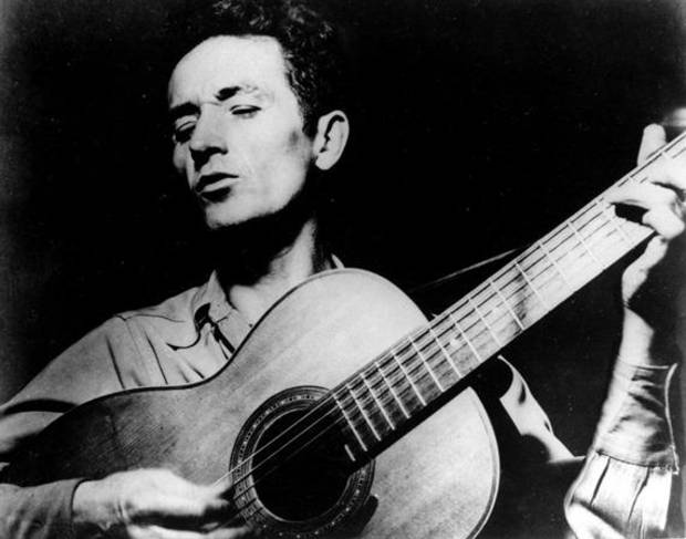 This undated file photo shows folk singer Woody Guthrie playing his guitar and singing. AP file photo