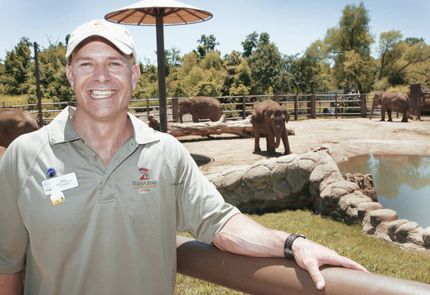 Mike Connolly, assistant curator of elephants at the Tulsa Zoo, stands in front of the elephant exhibit he runs. PHOTO BY DAVID MCDANIEL, THE OKLAHOMAN