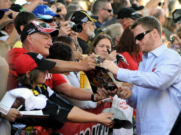 In this photo provided by the Las Vegas News Bureau, NASCAR driver Dale Earnhardt, Jr. signs autographs during Sprint Cup Series Champion's Week auto racing fanfest at Fremont Street Experience in Las Vegas on Wednesday, Nov. 28, 2012. (AP Photo/Las Vegas News Bureau, Brian Jones)