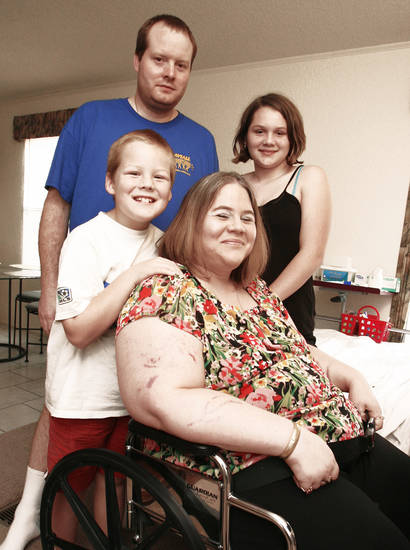 Crystal Ayers, seated, daughter Sam Ayers, 12, husband Richard Ayers and son Richard Ayers Jr., 8,  pose in their new double-wide mobile home. The family was inside another mobile home in the same park when a deadly tornado struck Lone Grove,  hurling them and their home about 150 feet and paralyzing Crystal.