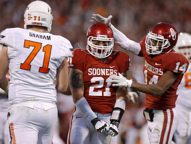 Oklahoma's Tom Wort (21) celebrates with Aaron Colvin (14) beside Oklahoma State's Parker Graham (71) during the Bedlam college football game between the University of Oklahoma Sooners (OU) and the Oklahoma State University Cowboys (OSU) at Gaylord Family-Oklahoma Memorial Stadium in Norman, Okla., Saturday, Nov. 24, 2012. Oklahoma won 51-48. Photo by Bryan Terry, The Oklahoman