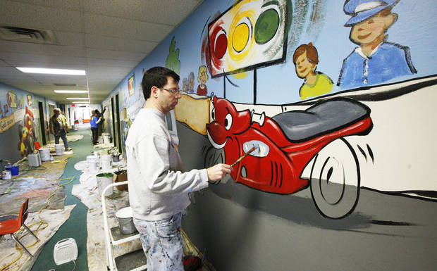 Joel Randell with Palmer Studios works on a mural at Oakcrest Church of Christ.
