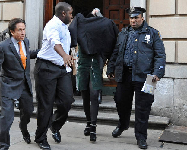 Lindsay Lohan, second from right, is escorted from the 10th Precinct police station, with her face shielded, Thursday, Nov. 29, 2012, in New York after being charged for allegedly striking a woman at a nightclub. Police say Lohan was arrested at 4 a.m. and charged with third-degree assault. They say she got into the argument with another woman at Club Avenue in Manhattan and struck the woman in face with her hand. (AP Photo/ Louis Lanzano)