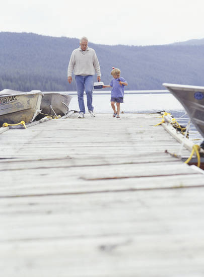 Grandfather and grandson (4-5) walking on pier at lake
