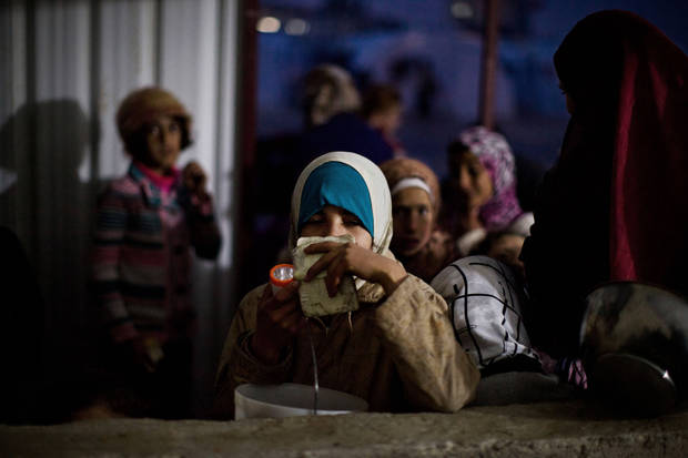 Syrian girls wait for food distribution at a refugee camp near the Turkish border, in Azaz, Syria, Sunday, Dec. 9, 2012. (AP Photo/Manu Brabo)